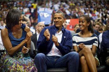 epa03308465 US President Barack Obama (C) does a little dance while First Lady Michelle Obama (L) and the President's daughter Malia(R) look on as they attend an exhibition basketball game between the USA and Brazil at the Verizon Center in Washington DC, USA, 16 July 2012. The President is back on the campaign trail on 17 July with a day-trip to Texas. EPA/JIM LO SCALZO